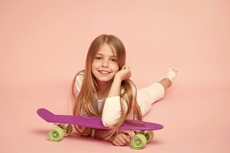 An extreme child. Small child relaxing at skateboard on pink background. Cute little child with violet penny board. Adorable girl child with skater style and look