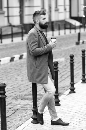 Waiting for someone in street. Man bearded hipster drink coffee paper cup. Businessman well groomed enjoy coffee break outdoors urban background. Enjoying coffee time. Walk and enjoy fresh hot coffee Banque d'images