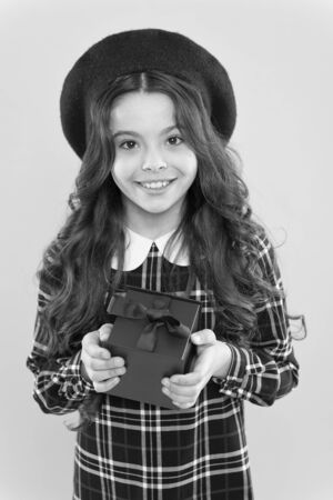 this is for you.parisian child on yellow background. happy birthday. . Holiday gift. shopping. child with present box. happy girl with long curly hair in beret. small girl in french style hat Stock Photo