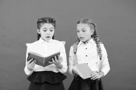 Reading opens doors. Small children reading books on red background. Adorable little girls learn reading at school. Cute pupils reading to learn important information 版權商用圖片