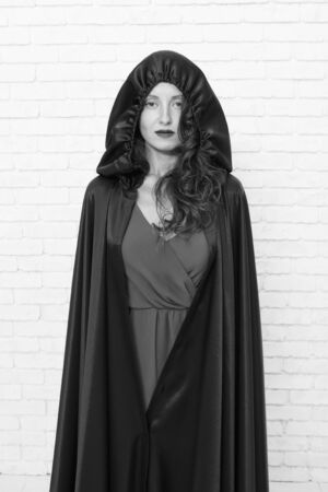 Her sorcery skills are just far too impressive. Halloween party girl. Sexy girl wearing hooded black cloak on white brickwall. Mysterious girl with classic witch look. A girl changed into a witch