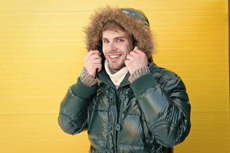 Comfortable winter clothing. Keep warm. Winter stylish menswear. Man bearded hipster wear warm jacket with fur yellow background. Guy wear warm jacket with hood. Feel comfortable in warm clothing