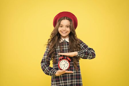 Good morning. Small child smiling in morning on yellow background. Happy little girl holding alarm clock early in the morning. Waking up in morning 写真素材 - 131977742