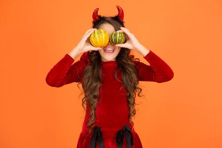 Playful imp. Girl with horns play with pumpkins. Happy holidays. Cute child celebrate Halloween. Autumn holidays. Pumpkins traditional attribute of fall holidays. Having fun. Decorations for holidays.