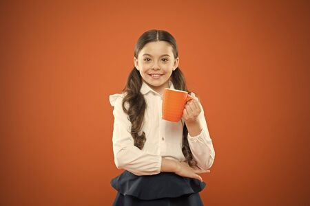 Kid tested breakfast. Little child having tea or milk for breakfast on orange background. Happy cute pupil holding book and drink for breakfast. Small girl smiling during her school breakfast