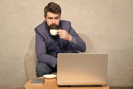 In mobile style. Bearded man enjoying his hot drink and mobile internet. Businessman with mobile device drinking tea or coffee at workplace. Hipster in formalwear working at laptop in mobile office