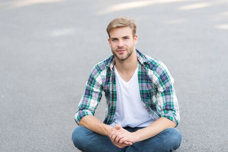 stay relaxed. handsome man checkered shirt. male fashion. student relax on road. macho guy outdoor. street style. man sit ground. carefree student guy. free time spending. summer fashion Stock Photo