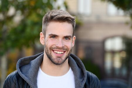 Perfect smile. Handsome guy portrait. Facial hair and skin care concept. Handsome face. Handsome man unshaven face and stylish hair. Caucasian man urban background. Bearded man in casual style