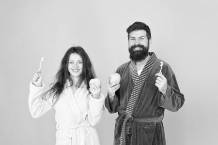 Personal hygiene. Couple in love cleaning teeth. Freshness and cleanliness. Keep teeth healthy. Healthy habits. Brush teeth every morning. Oral hygiene. Couple bathrobes hold toothbrushes and apples