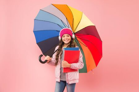 Rain forecast on September 1. Cute schoolgirl colorful umbrella on September 1. Small child go to library on September 1 on pink background. Little girl wear headset at first school day. September 1 Imagens