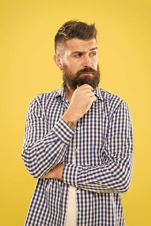 Bearded for your pleasure. Bearded man on yellow background. Bearded hipster touching his unshaven chin. Brutal caucasian guy with mustache and beard on bearded face