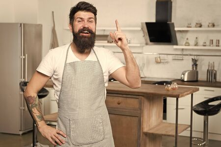 Got fresh idea about his recipe. Happy cook keeping finger raised in kitchen. Bearded chef following recipe to impress. Cooking dinner with traditional recipe. Preparing meal with cooking recipe