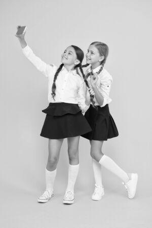 smile. digital technology. online education. knowledge day. happy friends with smartphone. kids make selfie photo, friendship. small girls in school uniform. back to school. educational blog Zdjęcie Seryjne