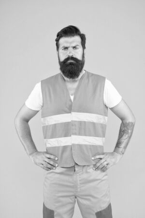 For a worker you can relay on. Confident worker on yellow background. Hard worker wearing work vest. Construction worker or road builder with long beard and mustache Zdjęcie Seryjne