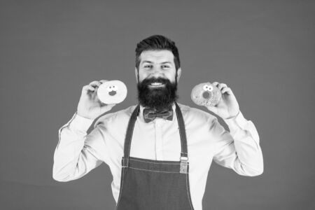 Bakery business. Baked goods. Sweets and cakes. Junk food. Hipster bearded baker hold donuts. Doughnut bakery. Glazed donut. Bearded cheerful well groomed man in apron selling donuts. Bakery owner Zdjęcie Seryjne