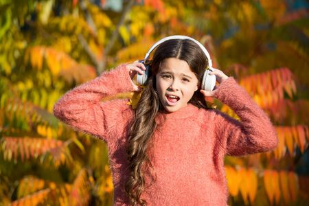 Listening audio best way help child improve vocabulary. Kid girl relaxing near autumn tree with headphones. Autumn walks with nice songs. Music for autumn mood. Listening song. Enjoy music fall day