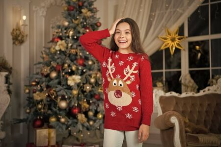 small happy girl at christmas. Christmas. Kid enjoy the holiday. Happy new year. morning before Xmas. New year holiday. little child girl likes xmas present. Christmas party time. favorite sweater 스톡 콘텐츠