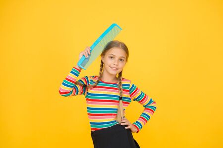 Haircare begins with combing. Little child hold hair comb yellow background. Haircare and combing. Haircare routine. Haircare to avoid clotted and tangle hair. Beauty hair salon
