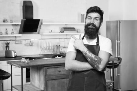 Kitchen furniture store. Cooking in new kitchen. Need culinary inspiration. Weekend begins from tasty breakfast. How to turn cooking at home into habit. Man bearded hipster red apron stand in kitchen Zdjęcie Seryjne