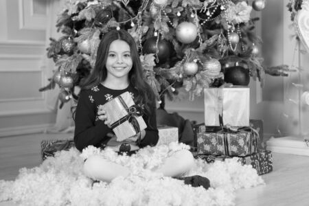 little child girl likes xmas present. Christmas. Kid enjoy the holiday. Happy new year. small happy girl at christmas. The morning before Xmas. New year holiday. Winter holidays sales. boxing day Zdjęcie Seryjne