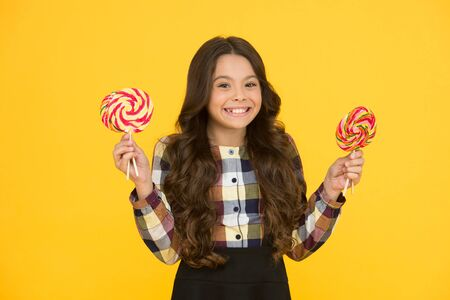 Lollipops make mouth happy. Little girl enjoy lollipops during school break. Happy small schoolchild eat lollipops. Large swirl lollipops on sticks. Sweet treat. Candy shop. Unhealthy eating