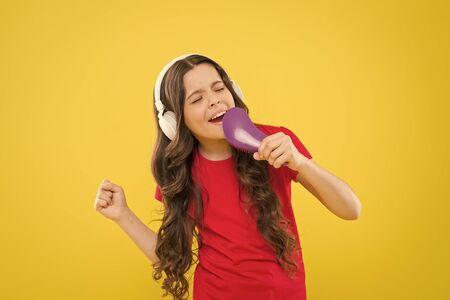 Karaoke star. Cute little girl pretending singing karaoke on yellow background. Adorable child performing karaoke song. Small singer performing karaoke soundtrack