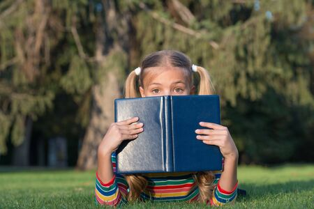 Dont judge book by its cover. Adorable small child cover face with book. Cute little girl read book on green grass. Great eye for good book. Banco de Imagens