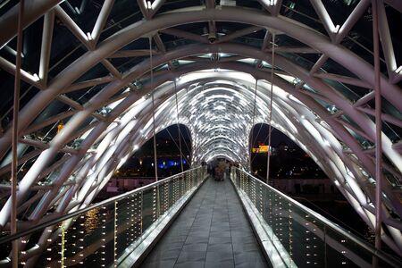 Pedestrian bridge. Steel glass construction illuminated numerous lights. Architecture concept. Bridge in Tbilisi. Curvy glass canopy top shimmers at night. Modern design bridge. Travel destinations.