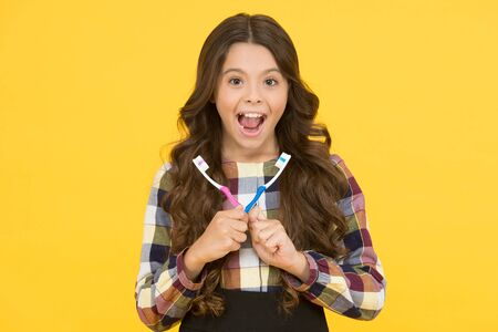 Be happy and healthy. Happy girl hold brushes on yellow background. Little child happy smiling with toothbrushes. Tooth health and hygiene. Daily routine. Lifestyle. Healthy is new happy