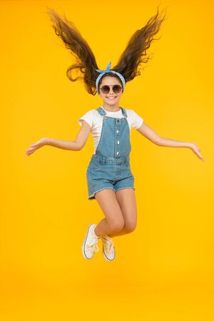 Amazing long hair. Cute small girl with long hair jumping on yellow background. Adorable little child enjoy long brunette hair. Best hairstyle for long hair. Beauty salon. Hairdressers parlor