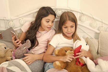 Is it for real. Little girls use smartphone in bed. Ordering gifts for Christmas and New Year by phone. Merry Christmas and Happy New Year greetings. Happy little children with mobile phone Stock Photo