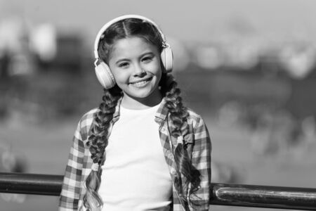 Music for the pure pleasure. Small child using technology for leisure or music education. Small kid enjoy listening to music. Small girl wearing stereo headphones. Small child with wireless headset