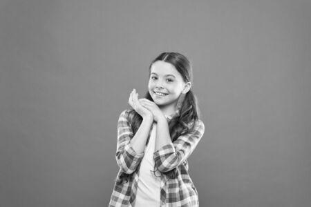 Here I am. kid fashion. smiling school girl. worker uniform. kid long hair. small girl checkered shirt. happy child. happy childrens day. childhood memory. little girl orange background