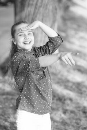 Happy small girl with adorable smiling face pointing at something. Little kid with cute smile shining with happiness. Happiness concept. The child of so much happiness and beauty 写真素材 - 132630294