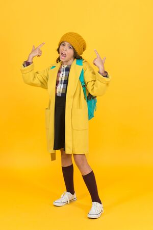 Unhappy small child hand gesturing on yellow background. Small schoolchild on autumn day. Small girl back to school. Adorable small child in autumn fashion