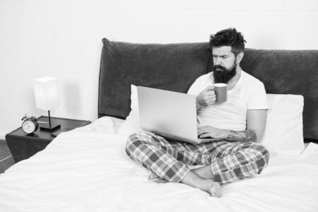 Just woke up and already at work. Hipster bearded guy pajamas freelance worker. Remote work concept. Social networks internet addiction. Online shopping. Man surfing internet or work online
