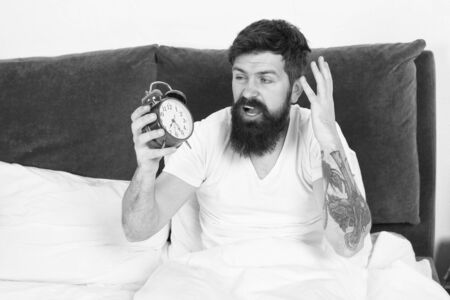 Get up with alarm clock. Overslept again. Tips for waking up early. Tips for becoming an early riser. Man bearded hipster sleepy face in bed with alarm clock. Problem with early morning awakening Stock fotó