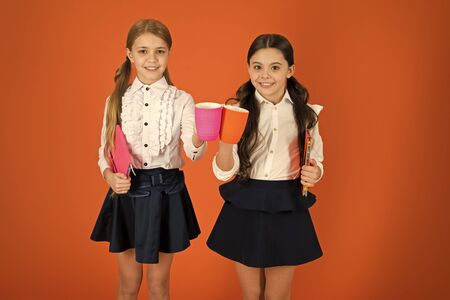 Tea for two and two for tea. Little children drinking morning tea or milk. Cute schoolgirls holding cups and books. Small girls enjoying school breakfast. School children having breakfast in morning