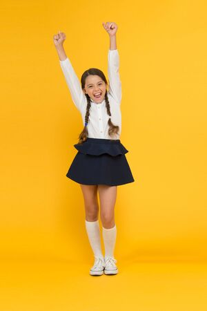 Celebrate knowledge day. September time to study. Girl adorable pupil on yellow background. School uniform and fashion. Back to school. Student little kid adores school. Emotional schoolgirl