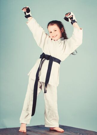 Karate fighter ready to fight. Karate sport concept. Self defence skills. Karate gives feeling of confidence. Strong and confident kid. She is dangerous. Girl little child in white kimono with belt