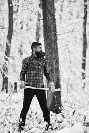 Man with warm gloves and checkered jacket in forest. Reklamní fotografie