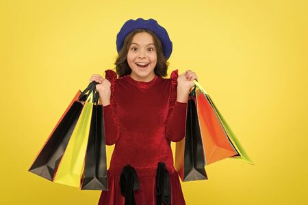 Birthday shopping concept. Child cute small girl on shopping tour. Best price. Buy now. Visit shopping mall. All i want for my birthday. Kid girl hold bunch shopping bags or birthday gifts packages