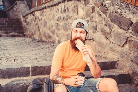 Urban lifestyle nutrition. Carefree hipster eat junk food while sit on stairs. Hungry man snack. Junk food. Guy eating hot dog. Man bearded enjoy quick snack and drink paper cup. Street food so good Zdjęcie Seryjne