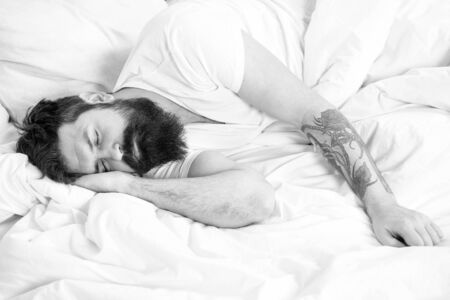 Lazy morning. Man bearded hipster sleepy in bed. Early morning hours. Insomnia and sleep problems. Relax and sleep concept. Man bearded guy sleep on white sheets. Healthy sleep and wellbeing.
