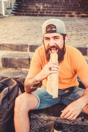Junk food. Guy eating hot dog. Man bearded enjoy quick snack. Street food so good. Urban lifestyle and unhealthy nutrition. Carefree hipster eat junk food while sit on stairs. Hungry man snack