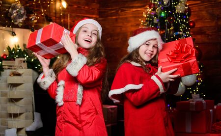 Best wishes. Little girl sisters in red hats. We are family. Elf children. Xmas present. Santa claus little girls sisters. Christmas time. Family holiday. Happy sisters. Happy new year. Family party
