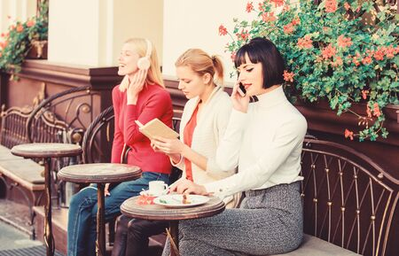 Female leisure. Weekend relax and leisure. Different interests. Hobby and leisure. Group pretty women cafe terrace entertain themselves with reading speaking and listening. Information source