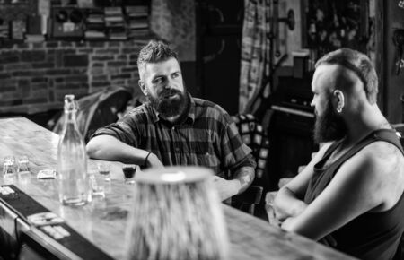 Friends relaxing in bar or pub. Hipster bearded man spend leisure with friend at bar counter. Men relaxing at bar. Strong alcohol drinks. Friday relaxation in bar. Opening hours till last visitors Standard-Bild
