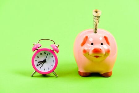 It is time to pay. Piggy bank stuffed dollar cash and alarm clock. Financial crisis. Banking account. Bankruptcy and debt. Pay for debt. Bank collector service. Credit debt. Economics and finance. Stockfoto