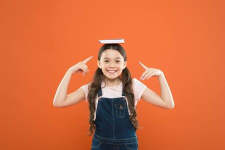 This is my book. writing notes. kid diary. happy little girl with notebook. school girl read book on orange background. literature lesson. back to school. poetry and novel. modern education